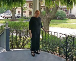 Bonnie Yates, 77, on the porch of her historic home in West Dundee, Illinois. The town is proposing a new taxing zone that will increase Yates' property taxes by more than $1,100 per year. The building across the street from her is a law firm. They are not included in the SSA, which will save them an estimated $1,450 per year.
